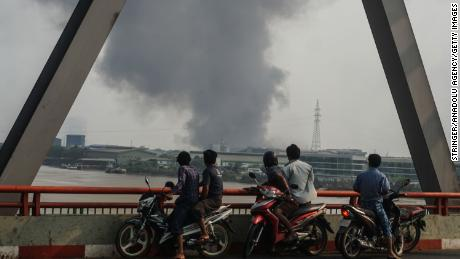 Smoke rises as protests against military coup and detention of elected government members continue in Hlaingtharya Township, Yangon, on March 14.