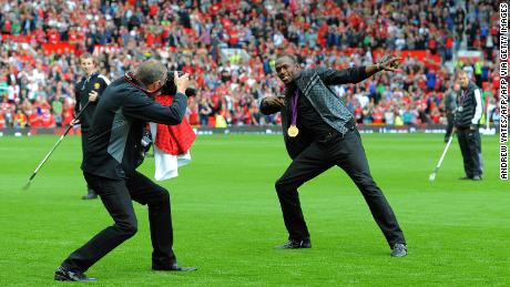 Usain Bolt recreates his famous celebration on the pitch at Old Trafford.