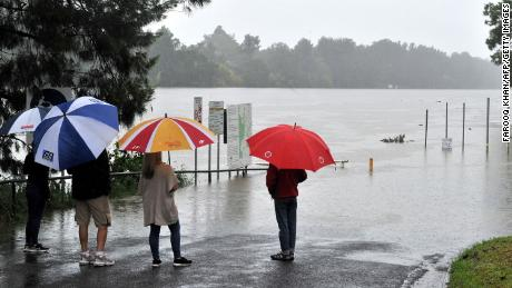 Residents look at the swollen Nepean river during heavy rain in western Sydney on March 20.