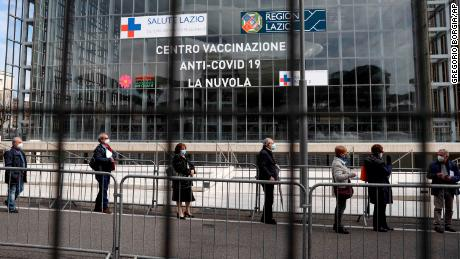 People queue to receive an AstraZeneca shot at a Rome convention center, temporarily turned into a Covid-19 vaccination hub, on Friday, March 19.