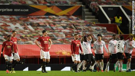 Manchester United players react as AC Milan players celebrate.