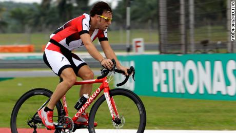 Alonso rides his bicycle around the Malaysia Grand Prix circuit while racing for Ferrari in 2013.