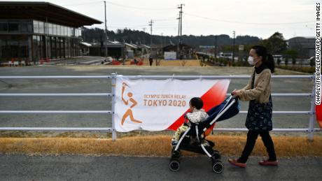 A woman pushes a child in a stroller outside a torch relay venue in Naraha town, March 25.