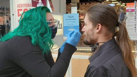 Zengota does a nose piercing on a customer at the Tacoma Mall.
