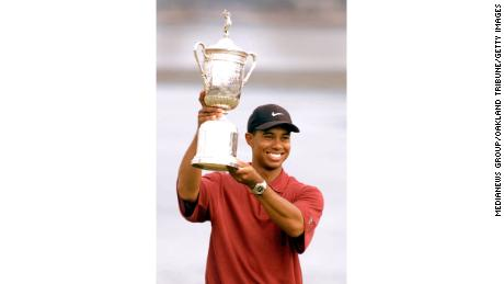 Woods holds up the U.S. Open trophy.