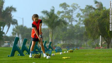 Pano lines up a shot on the driving range.