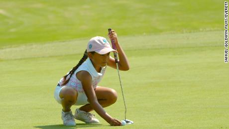 Avery lines up a putt.