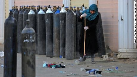 An Iraqi woman sweeps up debris Sunday next to oxygen bottles brought outside the Ibn Al-Khatib Hospital in Baghdad following Saturday night's fire.