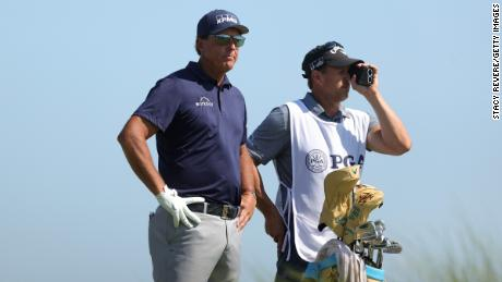 Mickelson looks on from the eighth tee with his caddie and brother Tim during the final round.
