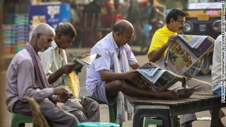 People read newspapers at a roadside tea stall in Patna, Bihar, India, on October 22, 2020.