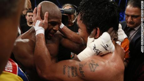 Mayweather hugs Manny Pacquiao after defeating him in their welterweight unification bout.