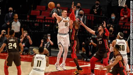 Jokic throws a no-look pass to Monte Morris as Robert Covington  of the Portland Trail Blazers defends.