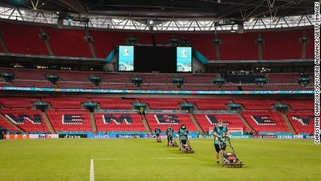 Groundkeepers work on the grass at Wembley Stadium after a match.
