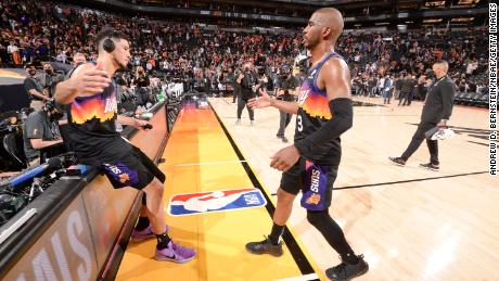 Booker high fives Paul after Game 1 against the Bucks.