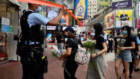 People hold flowers to mourn the death of the assailant.
