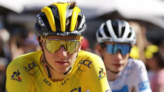 Tadej Pogacar of Slovenia wearing the overall leader's yellow jersey rides next to Team Jumbo Visma's Jonas Vingegaard of Denmark (R) wearing the best young's white jersey during the 21th and last stage of the 108th edition of the Tour de France cycling race.
