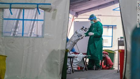 A medical personnel changes out an oxygen tank in a tent set up at a public hospital to handle the overflow of Covid-19 patients on June 24, 2021 in Jakarta, Indonesia.