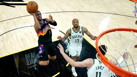 Phoenix Suns guard Chris Paul (3) shoots as Milwaukee Bucks forward P.J. Tucker (17) and center Brook Lopez (11) defend during the first half of Game 5 of basketball's NBA Finals, Saturday, July 17, 2021, in Phoenix.