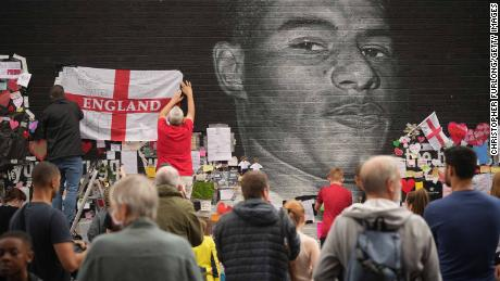 People look at the messages of support and the newly repaired mural of England footballer Marcus Rashford in Manchester, England.