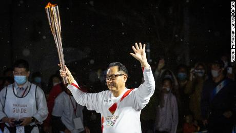 Toyoda runs with the Olympic torch during the Tokyo Olympic Games Torch Relay.