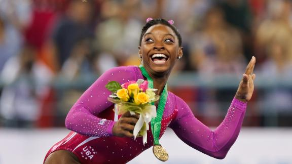 Biles dodges a bee flying near her during the medal ceremony after winning gold in the all-around final of the 2014 World Championships.