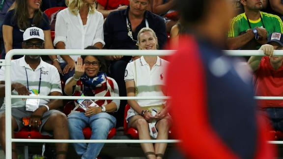 Biles' grandfather, Ron Biles, and his wife, Nellie, watch as she waits on the podium to receive her gold medal after winning the floor final of the 2016 Olympics. They took in Simone and her younger sister, Adria, and then formally adopted them when Simone was just 6 because Simone's mom was battling addiction to drugs and alcohol.