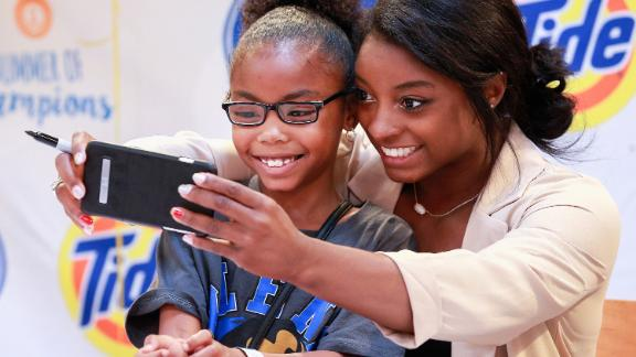 Biles takes a photo with a young fan in her hometown of Houston in September 2016.