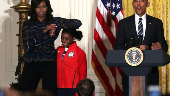 First lady Michelle Obama rests her elbow on Biles' head as President Barack Obama speaks during an Olympic athletes event at the White House in September 2016.