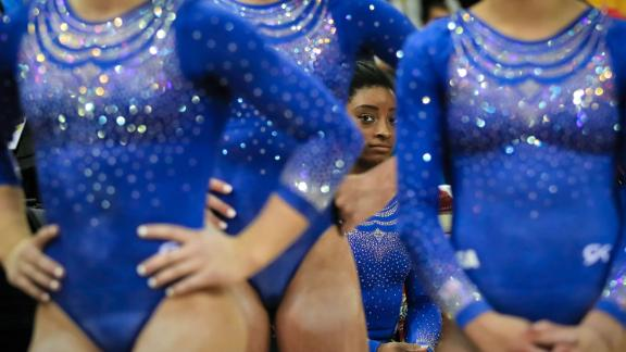 Biles rests behind teammates during qualifying sessions for the 2018 World Championships in Doha, Qatar.