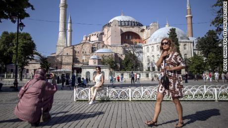 Tourists take pictures in front of the Hagia Sophia Mosque in Istanbul, Turkey on 27 June 2021. The reduction in tourism could cause unemployment to rise by as much as 10%, according to UNCTAD.