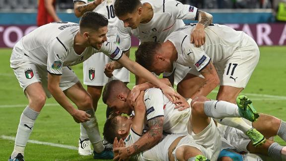 Nicolo Barella is mobbed by his teammates after scoring Italy's opening goal.