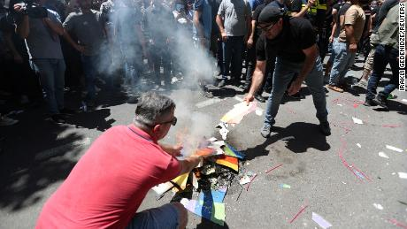 Anti-LGBT protesters burn a rainbow banner as they take part in a rally ahead of the march on Monday.