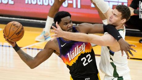 Phoenix Suns center Deandre Ayton (22) is defended by Milwaukee Bucks center Brook Lopez during the first half of Game 5 of basketball's NBA Finals, Saturday, July 17, 2021, in Phoenix.