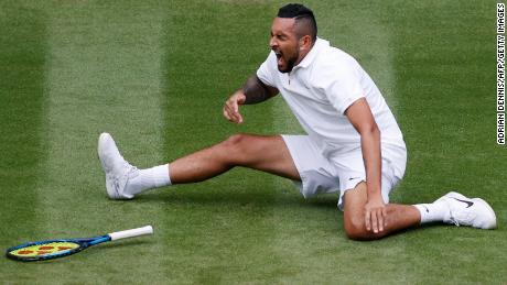 Australia's Nick Kyrgios falls as he returns to France's Ugo Humbert during their men's singles first round match on the third day of the 2021 Wimbledon Championships.