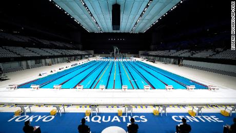 In this April 26, 2021, file photo, Tokyo 2020 Olympic Games Organizing staff prepare a swimming test event at the Tokyo Aquatics Center, one of the venues of the Tokyo 2020 Olympic and Paralympic Games, in Tokyo.