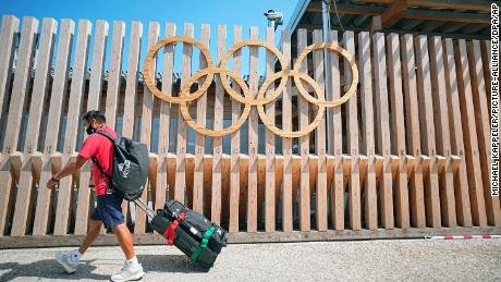 A member of the Mexican delegation walks past Olympic rings at the entrance to Olympic Village.