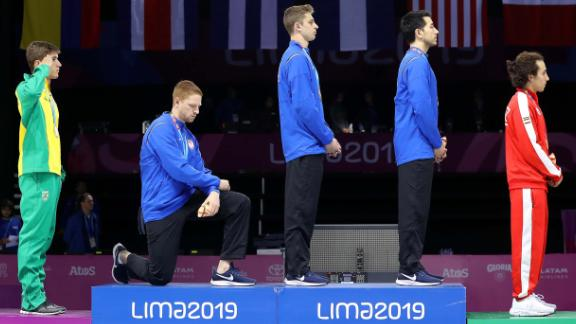 Race Imboden (third from left) takes the knee during the National Anthem Ceremony in the podium of men's foil team gold medal match at the 2019 Pan American Games in Lima, Peru.
