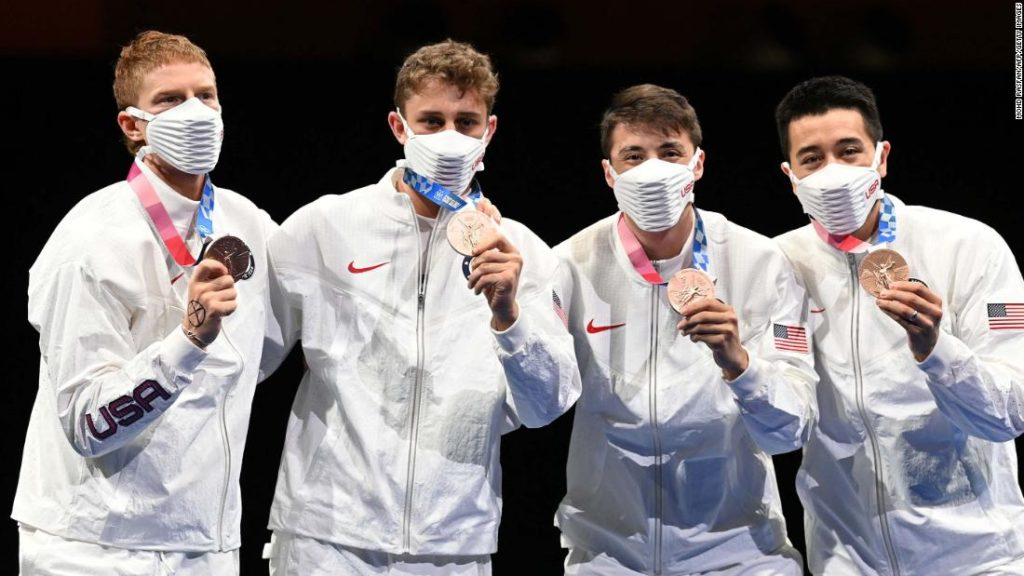 US Olympic fencer and bronze medalist wears X-symbol on hand on Olympic podium as a demonstration