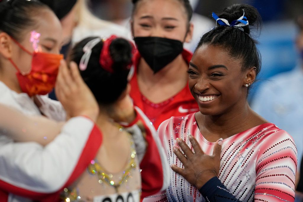 American gymnast Simone Biles smiles as China's Tang Xijing embraces teammate Guan Chenchen at the balance beam final on August 3.