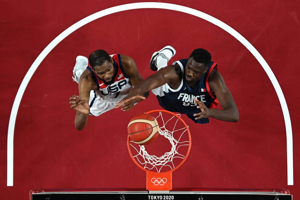 United States' Kevin Durant and France's Moustapha Fall battle in the men's basketball final on August 7.