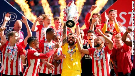 Brentford goalkeeper David Raya Martin lifts the trophy as they celebrate promotion to the Premier League after winning the Championship playoff final at Wembley Stadium.