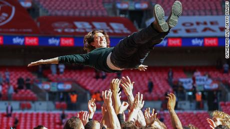 Brentford manager Thomas Frank is thrown in the air after the team's Championship playoff final success against Swansea City.