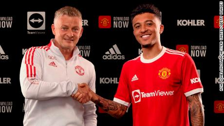 Jadon Sancho shakes hands with Manchester United manager Ole Gunnar Solskjaer after signing with the club.