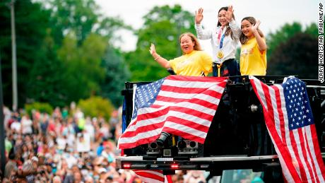 Suni Lee, center, waves from a St. Paul fire truck with her mom Yeev Thoj, left, and sister Shyenne Lee as fans cheer for her in a parade on August 8, 2021, in St. Paul, Minnesota.