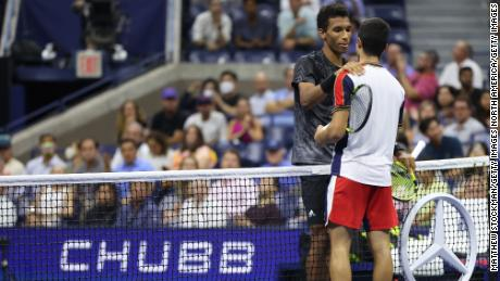 Felix Auger-Aliassime of Canada and Carlos Alcaraz of Spain meet at the net.
